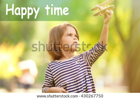 Little girl plays with wooden plane at the park.Concept of carefree childhood - stock photo