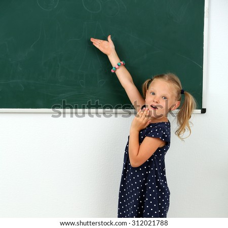 Little girl pointing at something at black chalkboard in classroom
