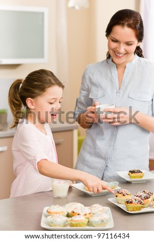 Little girl pointing cupcake to her mother happy at home - stock photo