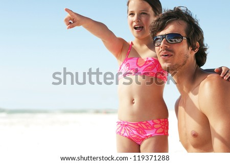 Little girl pointing out something of interest to her father looking down the beach - stock photo