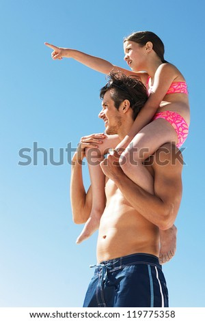 Little girl points to something in the distance with a cry of look over there dad - stock photo