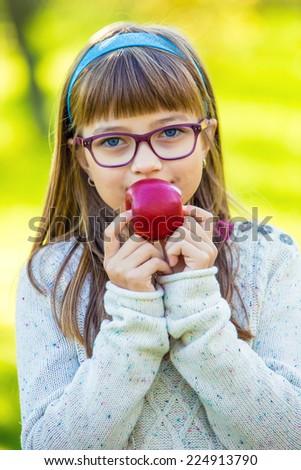 Little girl portrait eating red apple in garden. - stock photo
