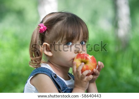Little girl portrait eating red apple outdoor - stock photo