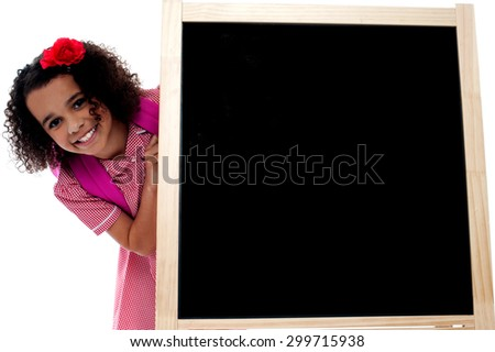 Little girl posing behind the black board - stock photo