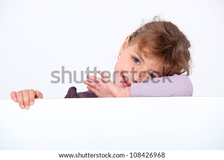 Little girl posing with blank advertisement board - stock photo