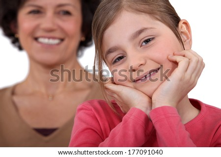 little girl posing with mother all smiles in background - stock photo