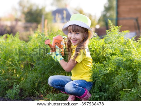 Little girl posing with watering can - stock photo