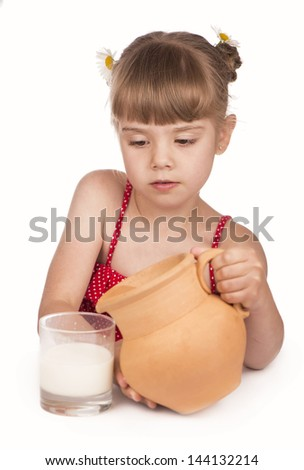 little girl pours milk from a jug