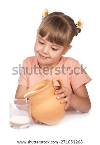 little girl pours milk from a jug - stock photo
