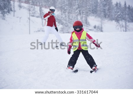 Little girl practicing skiing and her mother filming here with a mobile phone camera - stock photo