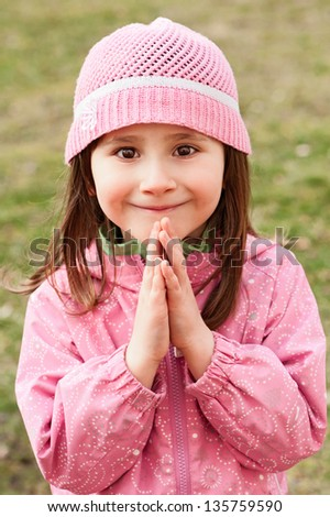 Little girl praying and smiling - closeup in the park - stock photo
