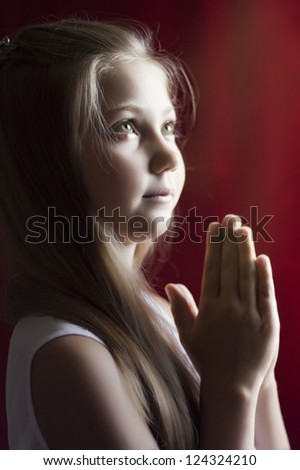little girl praying for their parents and peace - stock photo