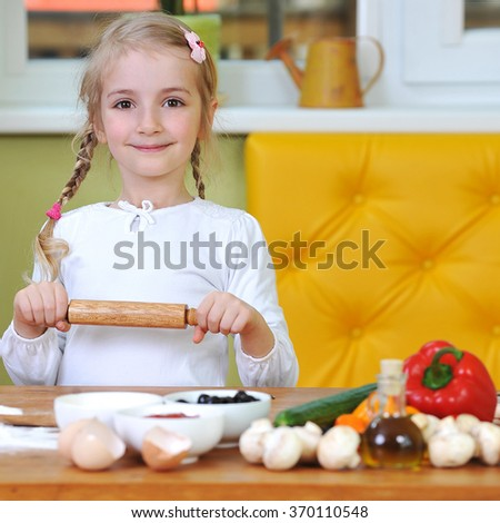 little girl prepare dough for pizzas - stock photo