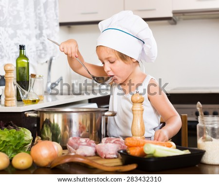 Little girl prepared soup with vegetables at kitchen