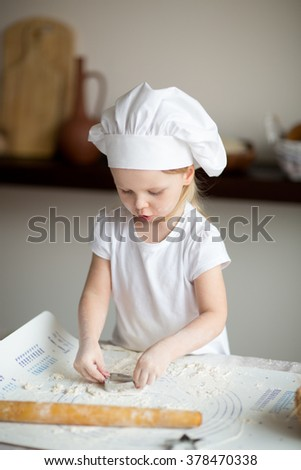 Little girl preparing bread with olives