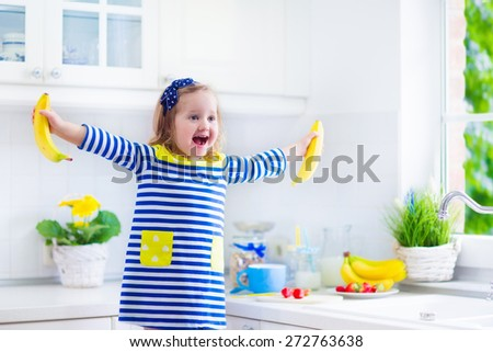 Little girl preparing breakfast in kitchen. Healthy food for children. Child drinking milk and eating fruit. Happy preschooler kid enjoys morning meal, cereal, banana and strawberry. Funny kids eating - stock photo
