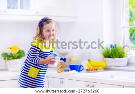 Little girl preparing breakfast in white kitchen. Healthy food for children. Child drinking milk and eating fruit. Happy smiling preschooler kid enjoying morning meal, cereal, banana and strawberry. - stock photo