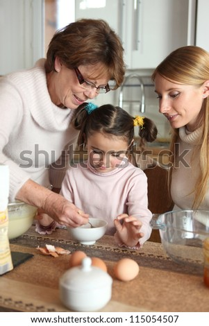 Little girl preparing cake with her mother and her grandmother
