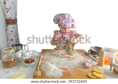 little girl preparing cakes in the kitchen on white background - stock photo