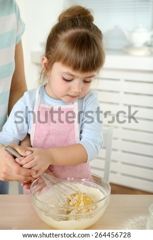Little girl preparing cookies with  mother in kitchen at home