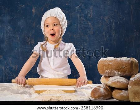 Little girl preparing dough for bread - stock photo