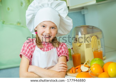 Little girl preparing fresh apple-carrot juice