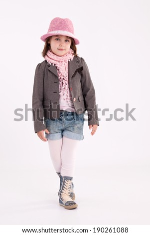 Little girl preschooler model in pink hat, coat, shorts and sneakers high with a scarf on her neck posing in studio - stock photo