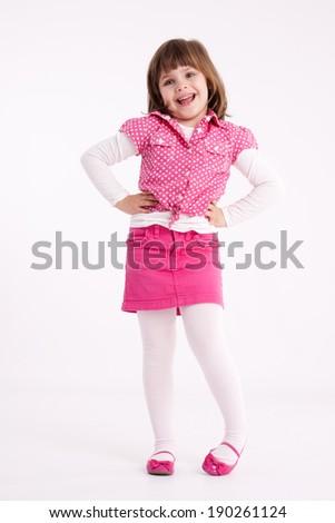 Little girl preschooler model in pink skirt, sandals and dotted shirt posing in studio - stock photo