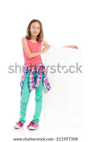 Little girl presenting white placard. Smiling girl standing close to blank banner.  - stock photo