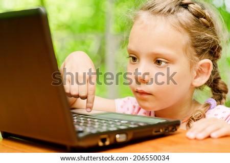 Little girl presses key on laptop - stock photo