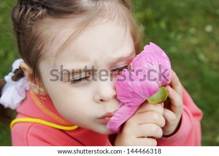 Little girl presses to cheek big pink flower - stock photo