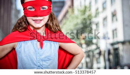 Little girl pretending to be a superhero against blur view of a modern city