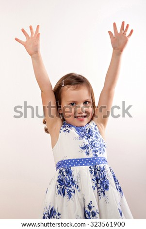 Little girl pulls her hands up, rejoicing - stock photo