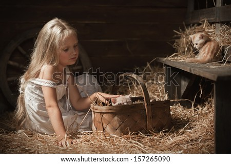 Little girl puts a kittens sleeping in a basket on hay in the barn