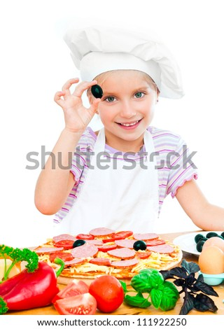 little girl puts olive on a pizza on white background