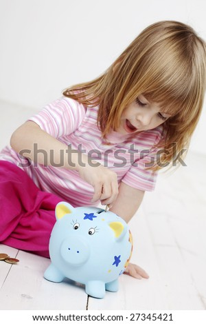 little girl putting money in her piggy bank, focus is mainly on the piggybank and hand - stock photo