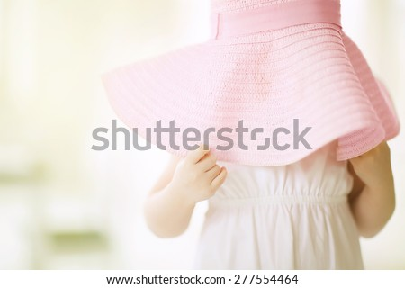 Little girl putting on large hat and hiding. - stock photo