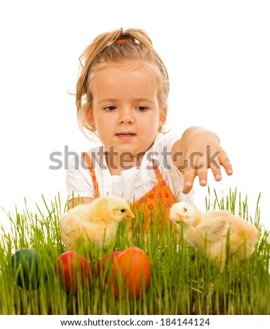 Little girl reaching for the easter eggs and little spring chickens - isolated