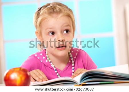 little girl reading a book at the table