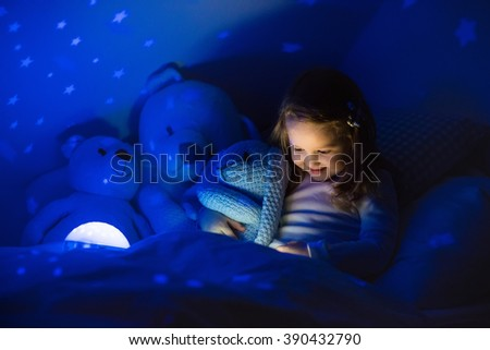 Little girl reading a book in bed. Dark bedroom with night light projecting stars on room ceiling. Kids nursery and bedding. Children read before bedtime. Toddler child playing with lamp and bear toy. - stock photo