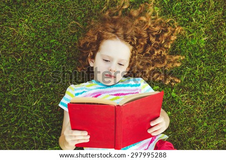 Little girl reading a book in the grass. Top view. - stock photo