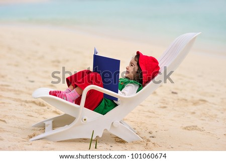 Little girl reading a book on a lounge chair at the beach - stock photo