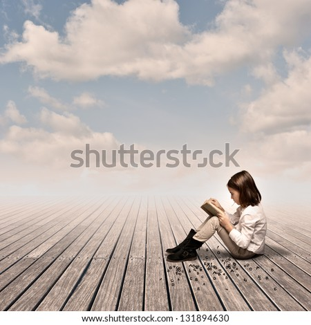 little girl reading a book on a wharf - stock photo
