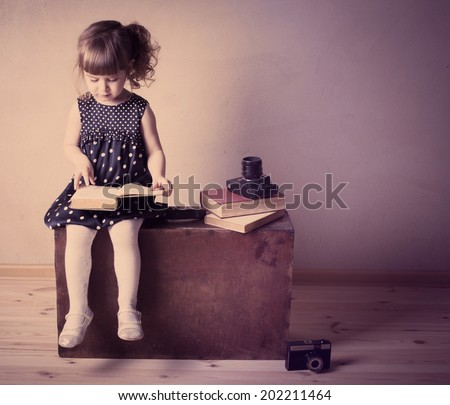 little girl reading a book on the old suitcase - stock photo