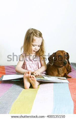 little girl reading a book  pet on the bed with multicolored bedspread, next   dog Dachshund