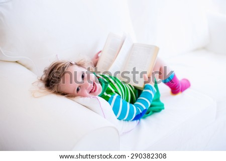 Little girl reading a book relaxing on a white couch. Kids read books at home or preschool. Children learning and doing homework after school. Child playing. Toddler kid in colorful dress on a sofa. - stock photo