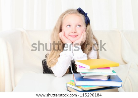 Little girl reading a book sitting on sofa