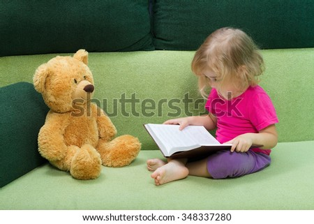 Little girl reading a book Teddy bear sitting on a green couch. - stock photo