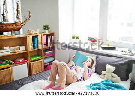 Little girl reading a book while lying in her bed - stock photo