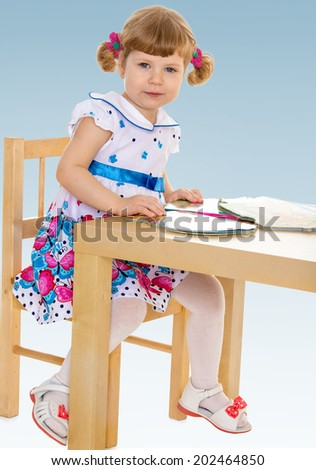 little girl reading a book while sitting at table/passionate child for interesting occupation,active lifestyle,happiness concept,carefree childhood concept.